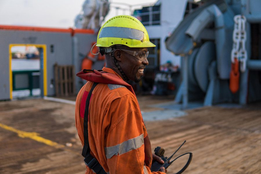 Seaman AB or Bosun on deck of offshore vessel or ship , wearing PPE personal protective equipment - helmet, coverall, lifejacket, goggles.