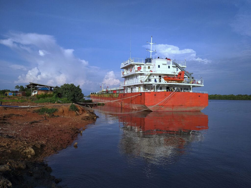 Palm oil tanker loading at an Indonesian river jetty
